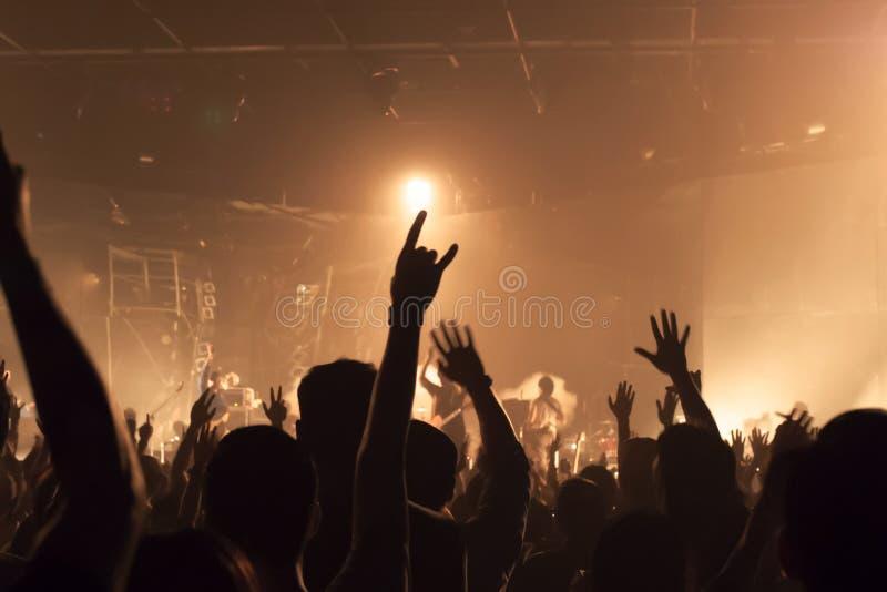 La banda di musica ammucchia sollevando le mani su nell'aria immagini stock libere da diritti