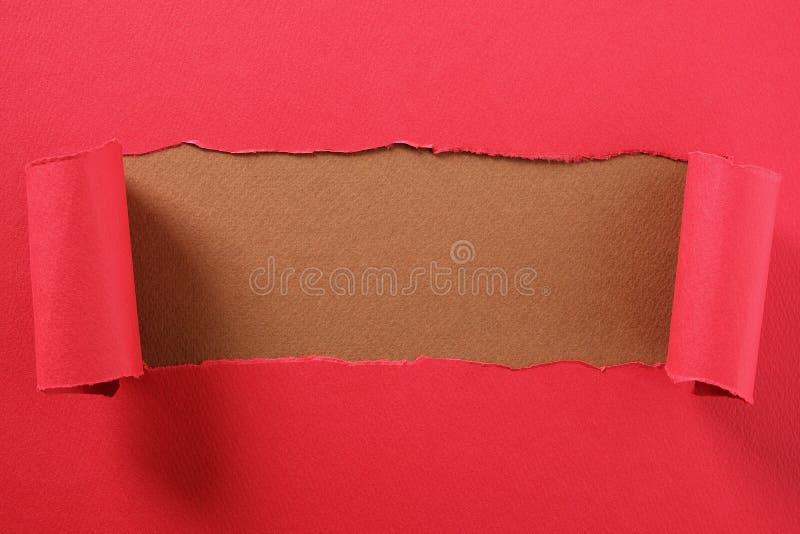 La bande de papier rouge déchirée a courbé le fond brun de indication de centre de bord images libres de droits