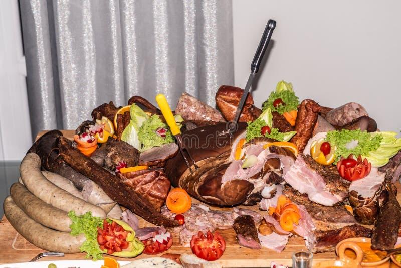 La bandeja de la comida de la carne con los pedazos de jamón cortado, de tomates de la salchicha y de salchicha vegetal del corte fotografía de archivo libre de regalías