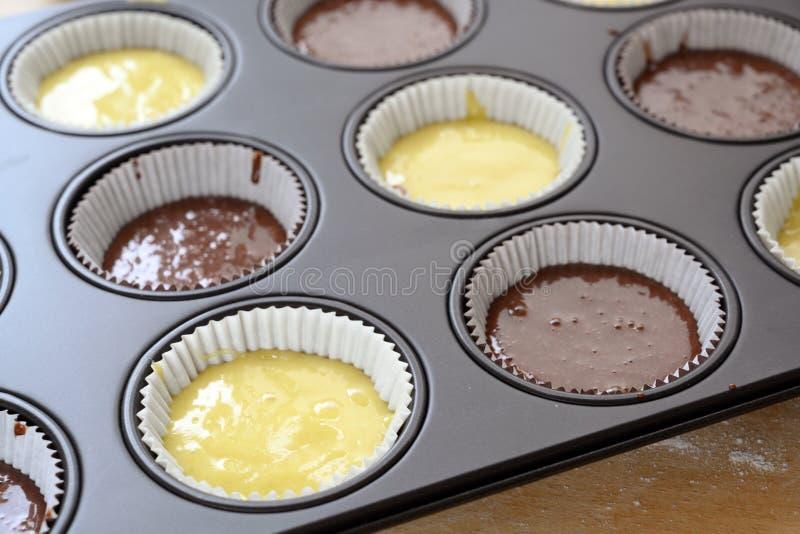 La bandeja que cocía del mollete llenó de dos clases de pasta, de luz y de chocolate de la torta para las magdalenas deliciosas fotos de archivo