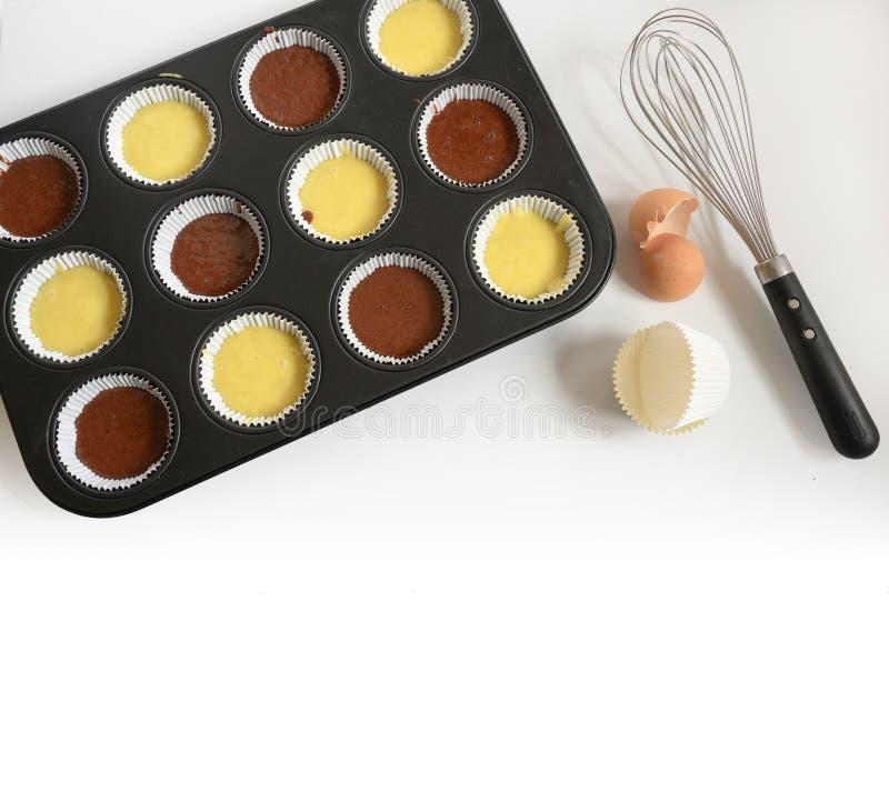 La bandeja que cuece del mollete llenada de la pasta ligera y oscura de la torta para las tazas de las magdalenas, del batidor, d fotos de archivo