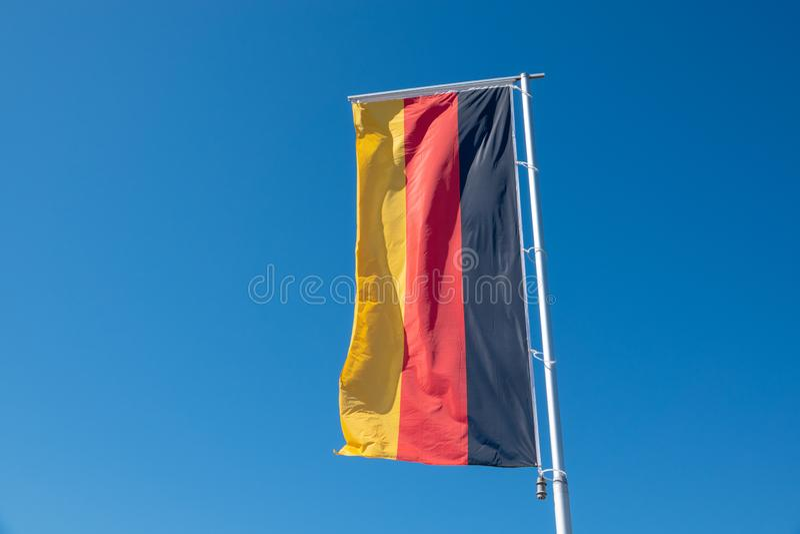 La bandera alemana sopla delante de un cielo azul imagen de archivo