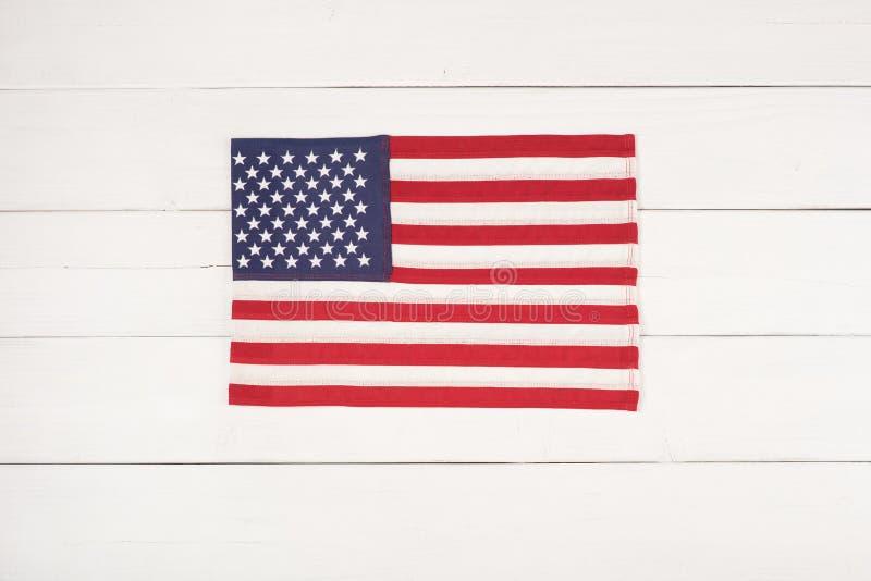 La bandera americana del rojo, blanca y azul en el centro en de la falsa madera texturizada pintada, rústica blanca sube al fondo fotografía de archivo