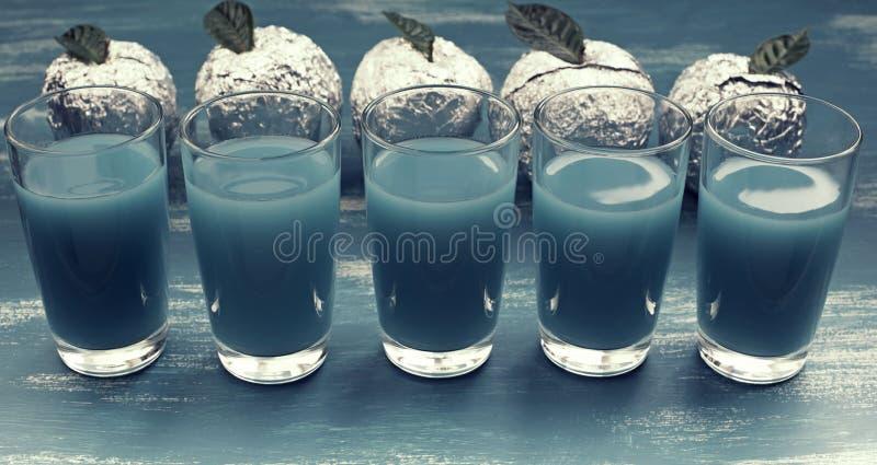 La bandera cinco vidrios del surrealismo azul Apple de la bebida Foil el fondo lamentable azul fotos de archivo