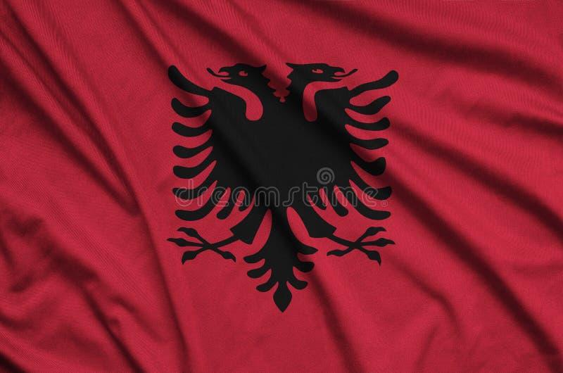 La bandera de Albania se representa en una tela del paño de los deportes con muchos dobleces Bandera del equipo de deporte fotos de archivo libres de regalías