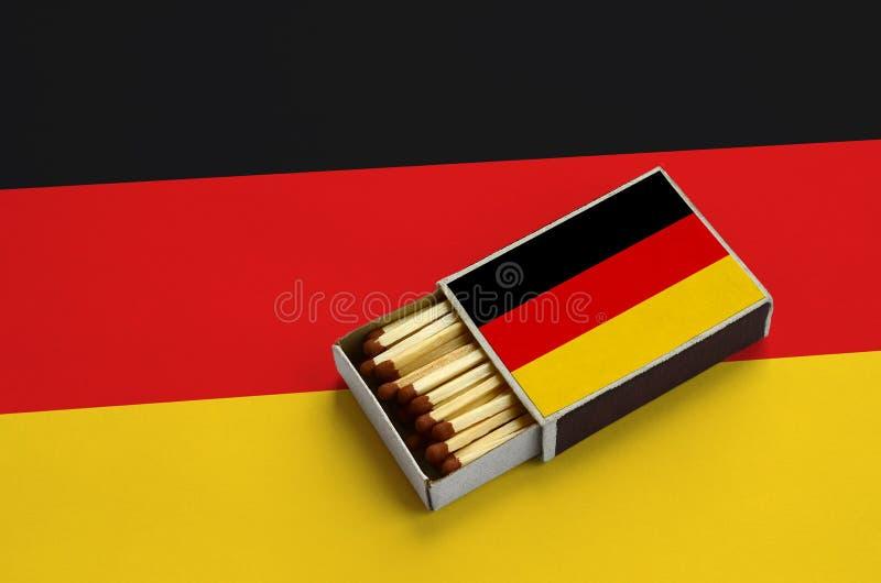 La bandera de Alemania se muestra en una caja de cerillas abierta, que se llena de los partidos y miente en una bandera grande fotos de archivo