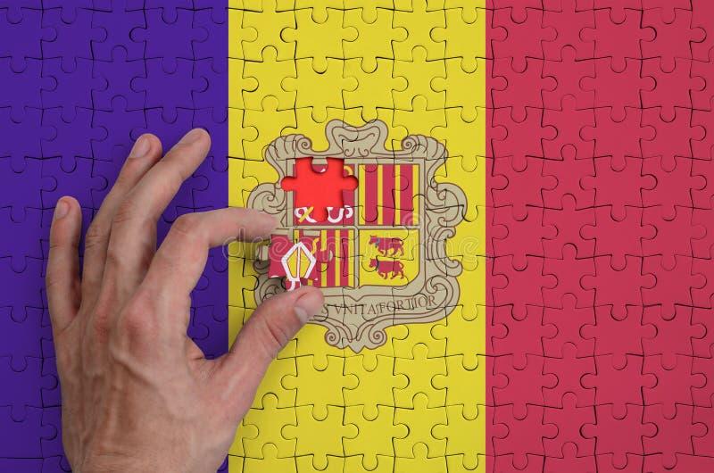 La bandera de Andorra se representa en un rompecabezas, que la mano del ` s del hombre termina para doblar fotos de archivo