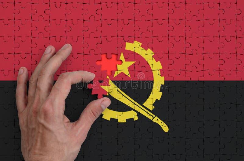 La bandera de Angola se representa en un rompecabezas, que la mano del ` s del hombre termina para doblar fotografía de archivo libre de regalías