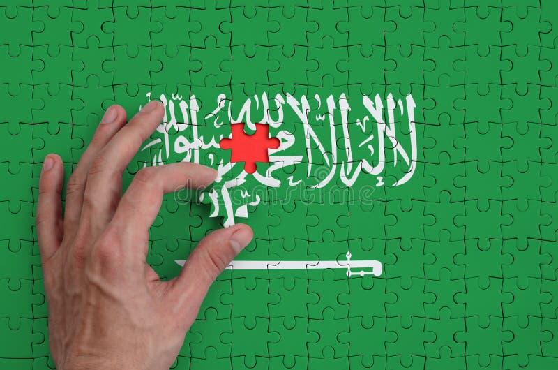 La bandera de la Arabia Saudita se representa en un rompecabezas, que la mano del ` s del hombre termina para doblar fotografía de archivo libre de regalías