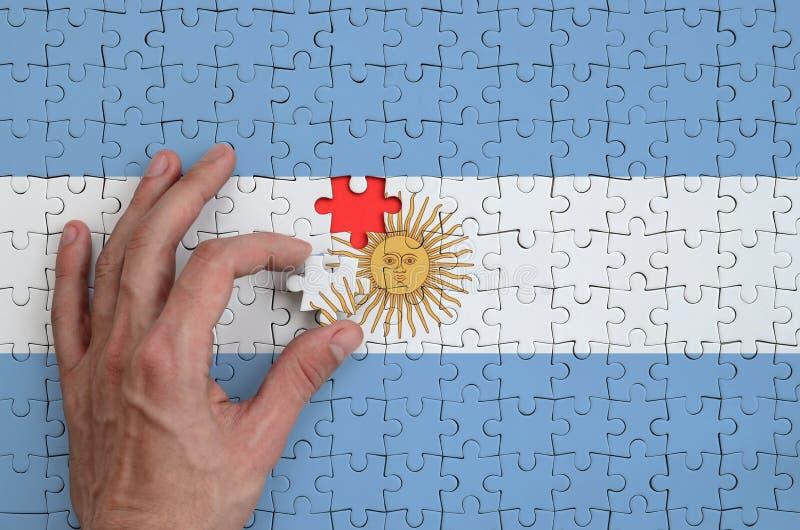 La bandera de la Argentina se representa en un rompecabezas, que la mano del ` s del hombre termina para doblar imagenes de archivo