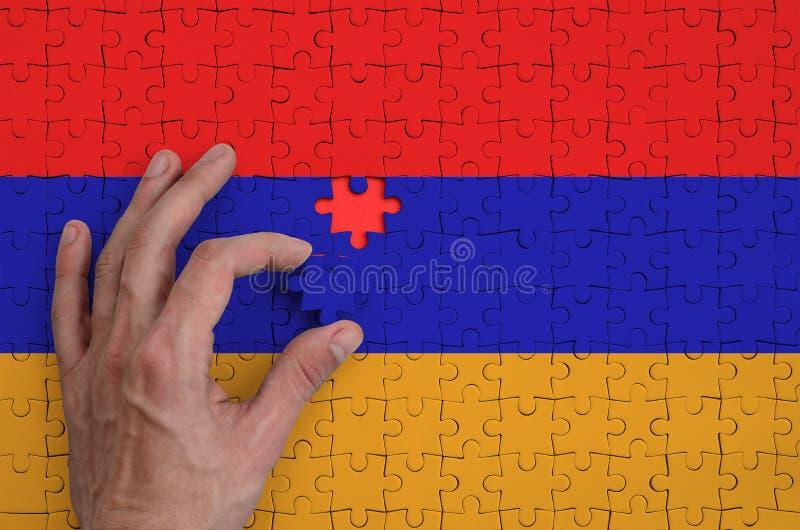 La bandera de Armenia se representa en un rompecabezas, que la mano del ` s del hombre termina para doblar imagenes de archivo
