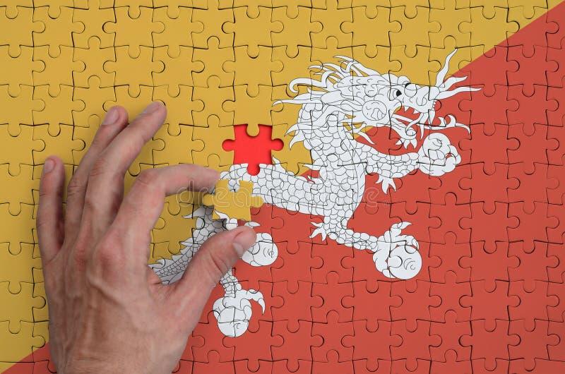 La bandera de Bhután se representa en un rompecabezas, que la mano del ` s del hombre termina para doblar imagen de archivo