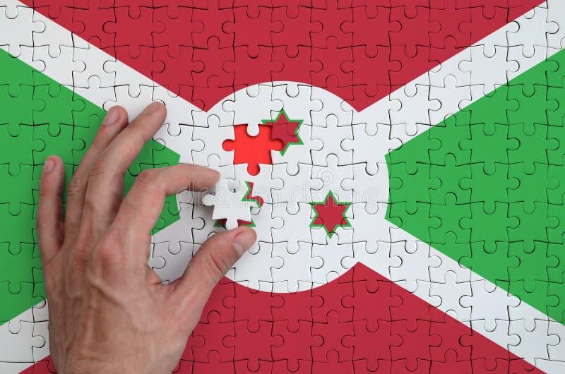 La bandera de Burundi se representa en un rompecabezas, que la mano del ` s del hombre termina para doblar fotos de archivo