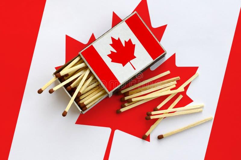 La bandera de Canadá se muestra en una caja de cerillas abierta, de la cual varios partidos caen y las mentiras en una bandera gr fotografía de archivo