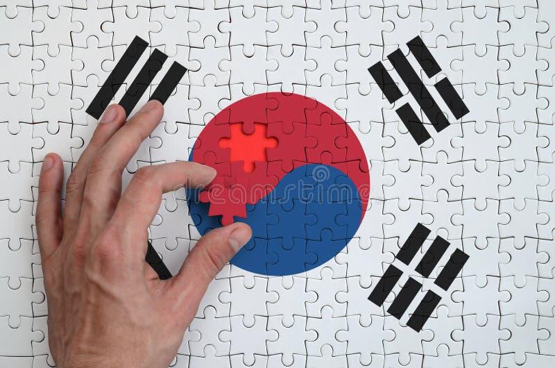 La bandera de la Corea del Sur se representa en un rompecabezas, que la mano del ` s del hombre termina para doblar foto de archivo libre de regalías