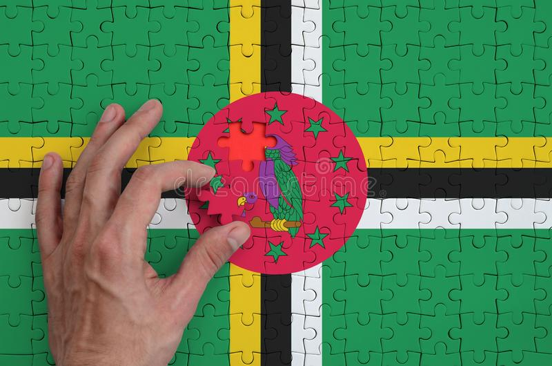 La bandera de Dominica se representa en un rompecabezas, que la mano del ` s del hombre termina para doblar imagenes de archivo