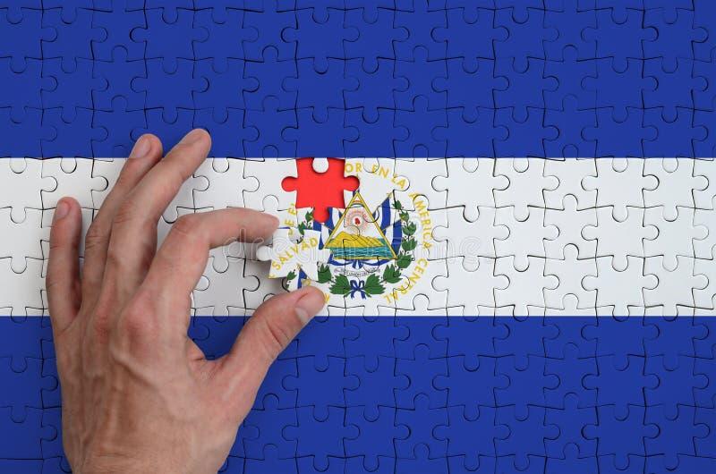 La bandera de El Salvador se representa en un rompecabezas, que la mano del ` s del hombre termina para doblar imagen de archivo libre de regalías