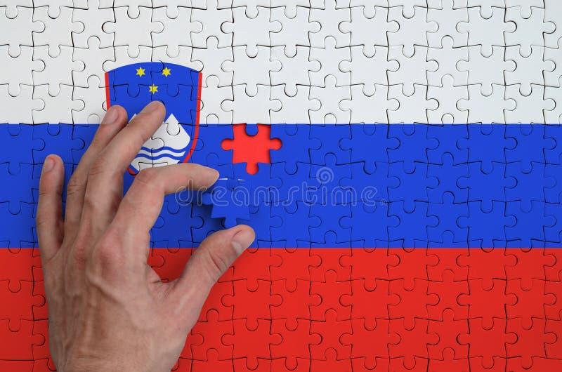 La bandera de Eslovenia se representa en un rompecabezas, que la mano del ` s del hombre termina para doblar imagenes de archivo
