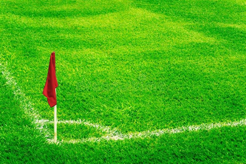 La bandera de la esquina roja en un campo de fútbol con la hierba verde fresca brillante del césped y el fútbol blanco tocan líne fotografía de archivo