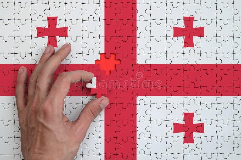 La bandera de Georgia se representa en un rompecabezas, que la mano del ` s del hombre termina para doblar imágenes de archivo libres de regalías