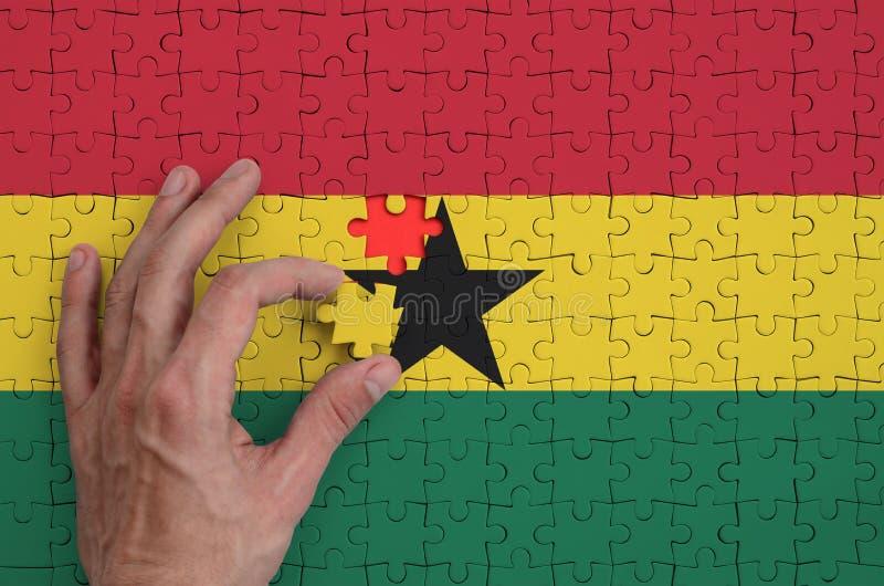 La bandera de Ghana se representa en un rompecabezas, que la mano del ` s del hombre termina para doblar foto de archivo