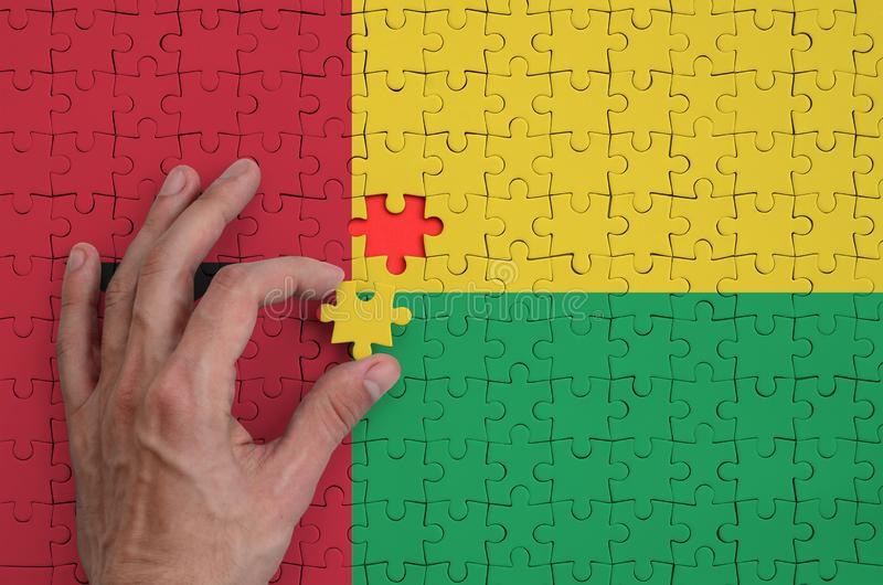 La bandera de Guinea-Bissau se representa en un rompecabezas, que la mano del ` s del hombre termina para doblar fotografía de archivo libre de regalías