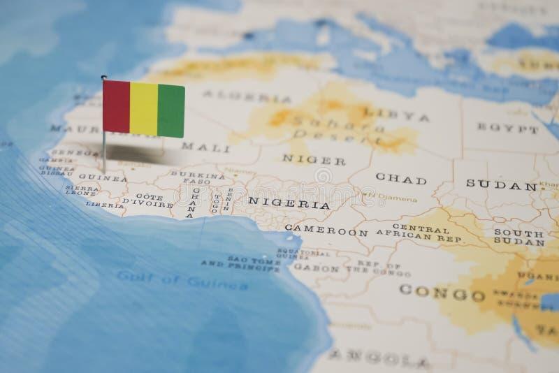 La bandera de Guinea en el mapa del mundo imagenes de archivo