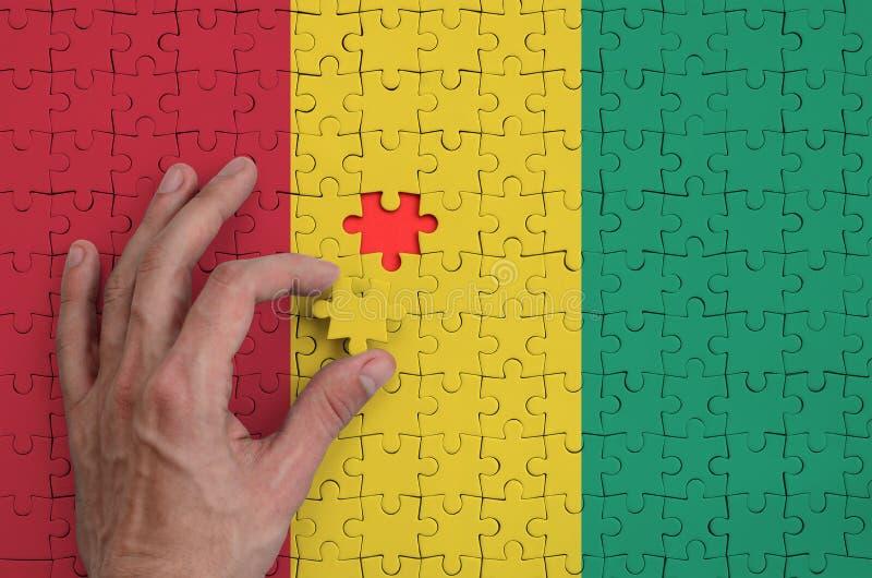 La bandera de Guinea se representa en un rompecabezas, que la mano del ` s del hombre termina para doblar fotos de archivo