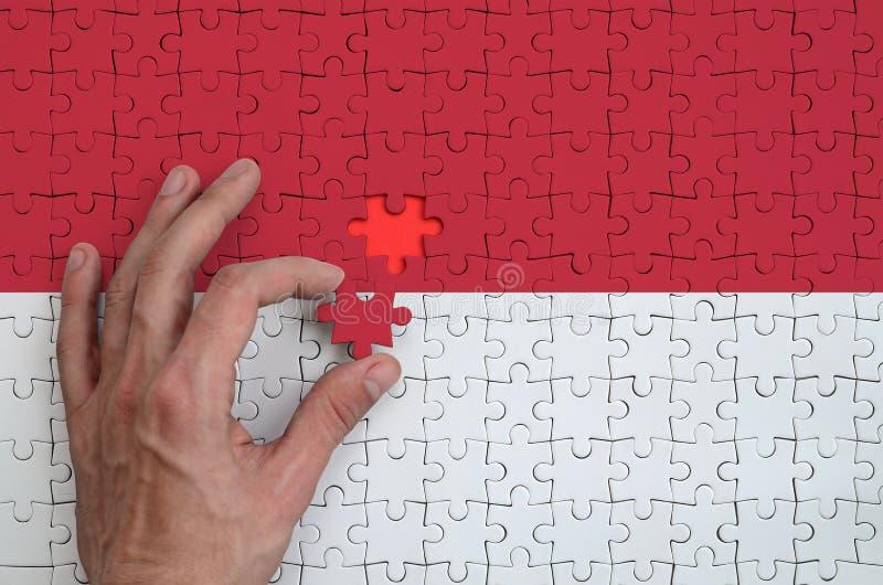 La bandera de Indonesia se representa en un rompecabezas, que la mano del ` s del hombre termina para doblar fotos de archivo libres de regalías