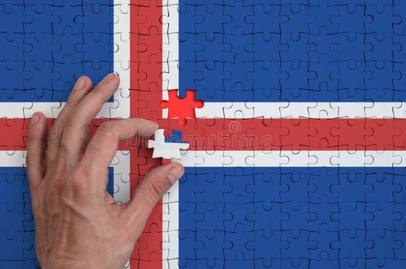 La bandera de Islandia se representa en un rompecabezas, que la mano del ` s del hombre termina para doblar fotos de archivo