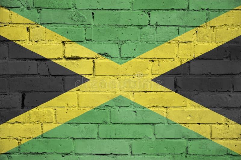 La bandera de Jamaica se pinta sobre una pared de ladrillo vieja imagen de archivo libre de regalías