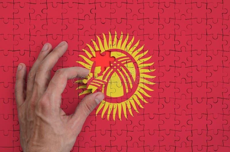 La bandera de Kirguistán se representa en un rompecabezas, que la mano del ` s del hombre termina para doblar fotos de archivo libres de regalías