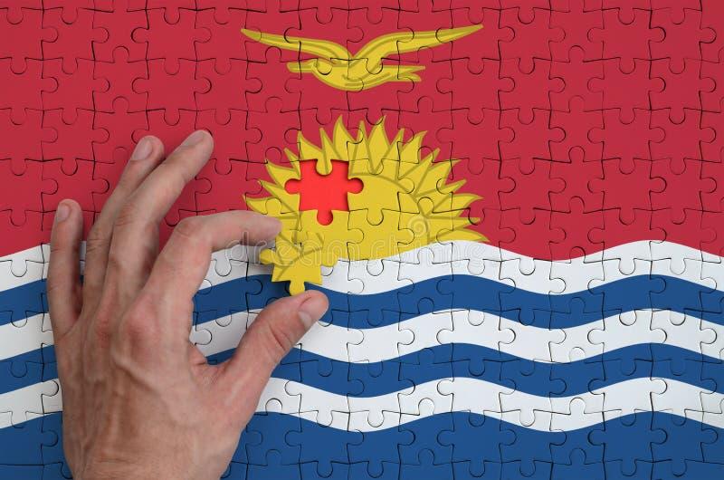 La bandera de Kiribati se representa en un rompecabezas, que la mano del ` s del hombre termina para doblar fotografía de archivo