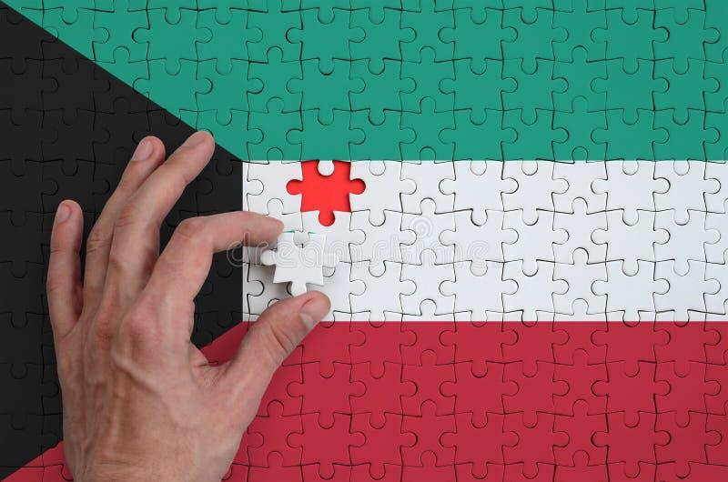 La bandera de Kuwait se representa en un rompecabezas, que la mano del ` s del hombre termina para doblar fotos de archivo