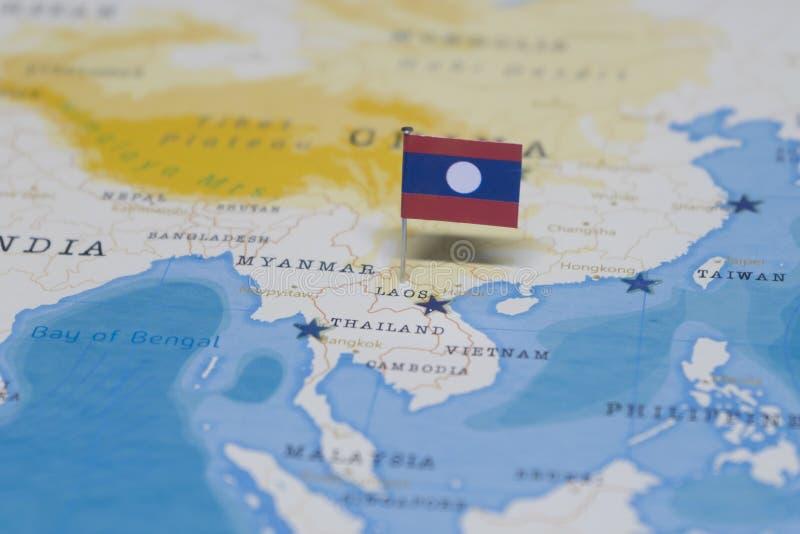 La bandera de Laos en el mapa del mundo fotos de archivo