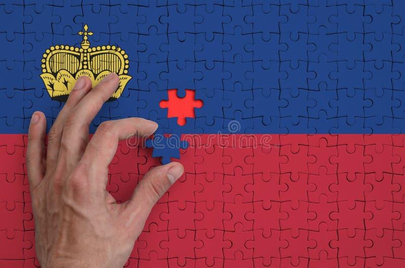 La bandera de Liechtenstein se representa en un rompecabezas, que la mano del ` s del hombre termina para doblar fotografía de archivo libre de regalías