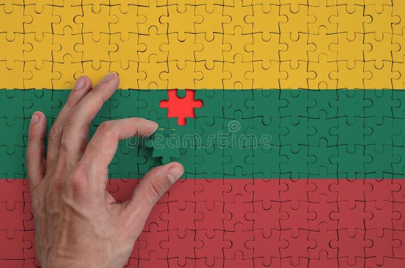 La bandera de Lituania se representa en un rompecabezas, que la mano del ` s del hombre termina para doblar foto de archivo libre de regalías