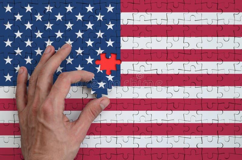 La bandera de los Estados Unidos de América se representa en un rompecabezas, que la mano del ` s del hombre termina para doblar imagen de archivo