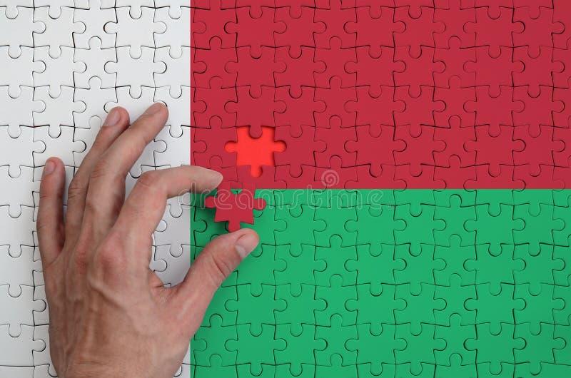 La bandera de Madagascar se representa en un rompecabezas, que la mano del ` s del hombre termina para doblar fotografía de archivo libre de regalías