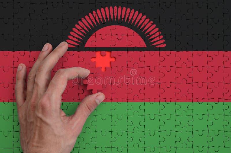 La bandera de Malawi se representa en un rompecabezas, que la mano del ` s del hombre termina para doblar fotos de archivo