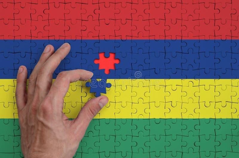 La bandera de Mauricio se representa en un rompecabezas, que la mano del ` s del hombre termina para doblar foto de archivo libre de regalías