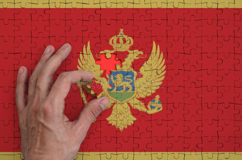 La bandera de Montenegro se representa en un rompecabezas, que la mano del ` s del hombre termina para doblar fotos de archivo