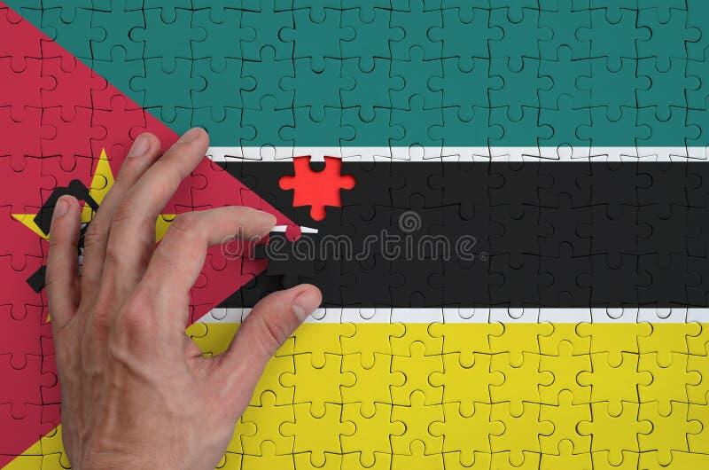 La bandera de Mozambique se representa en un rompecabezas, que la mano del ` s del hombre termina para doblar fotos de archivo libres de regalías