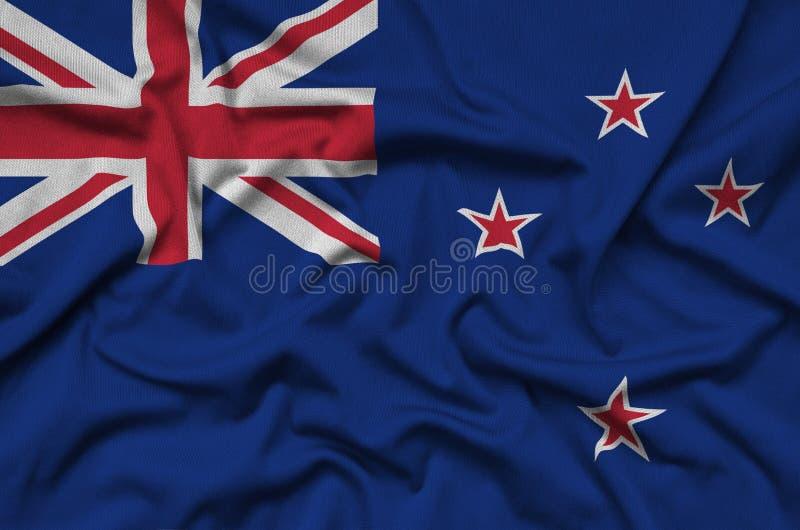 La bandera de Nueva Zelanda se representa en una tela del paño de los deportes con muchos dobleces Bandera del equipo de deporte imagen de archivo libre de regalías