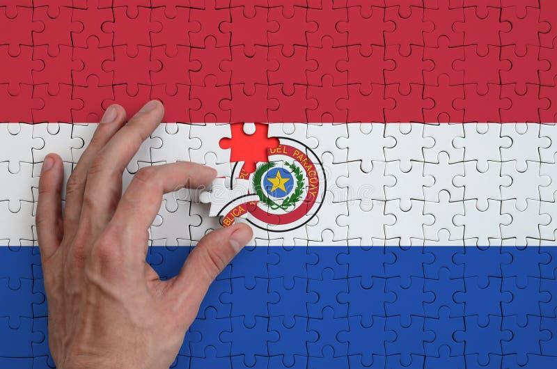 La bandera de Paraguay se representa en un rompecabezas, que la mano del ` s del hombre termina para doblar fotos de archivo libres de regalías
