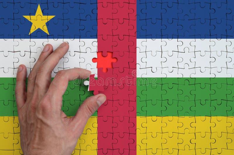 La bandera de la República Centroafricana se representa en un rompecabezas, que la mano del ` s del hombre termina para doblar fotografía de archivo