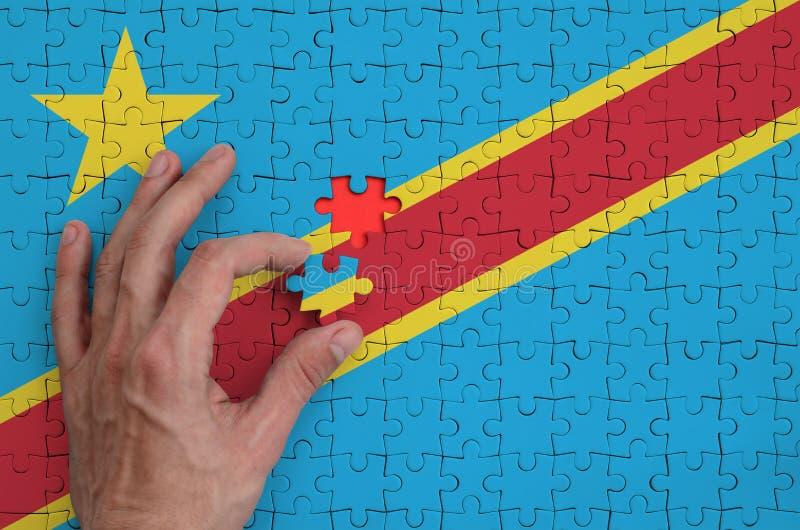 La bandera de República Democrática del Congo se representa en un rompecabezas, que la mano del ` s del hombre termina para dobla foto de archivo