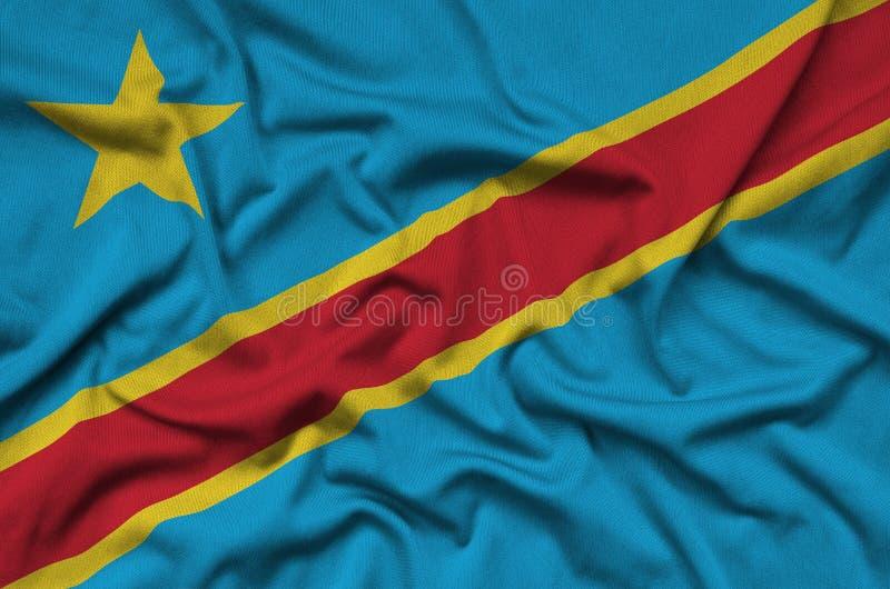 La bandera de República Democrática del Congo se representa en una tela del paño de los deportes con muchos dobleces Bandera del  imagen de archivo libre de regalías