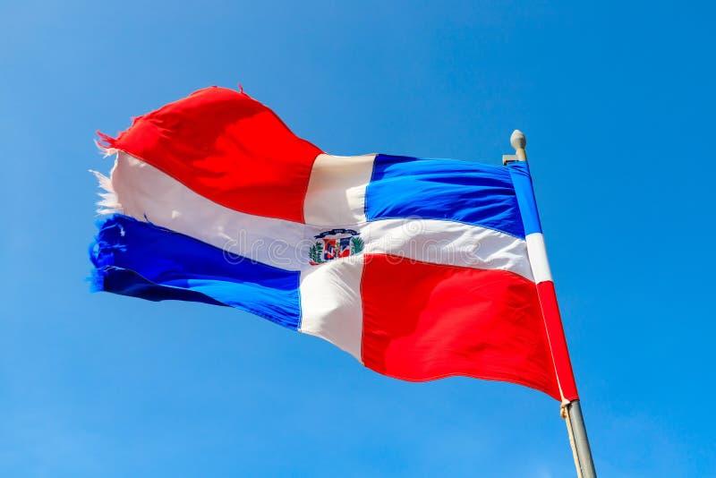 La bandera de la República Dominicana está agitando antes de un cielo azul imagen de archivo libre de regalías