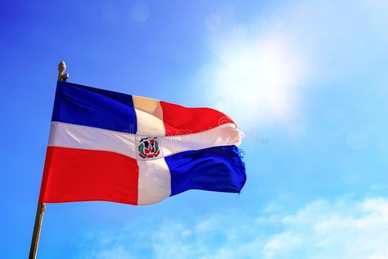 La bandera de la República Dominicana está agitando antes de un cielo azul con los rayos de sol que brillan a través foto de archivo